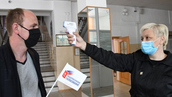 Измерение температуры участника голосования по внесению поправок в Конституцию РФ на избирательном участке №209 в Чите