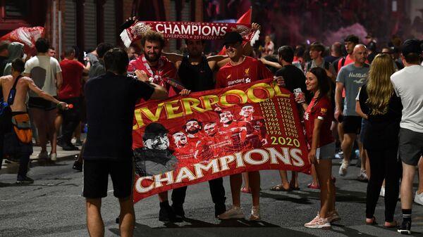 Болельщики Ливерпуля празднуют победу своей команды в чемпионате Англии по футболу у домашнего стадиона Энфилд
