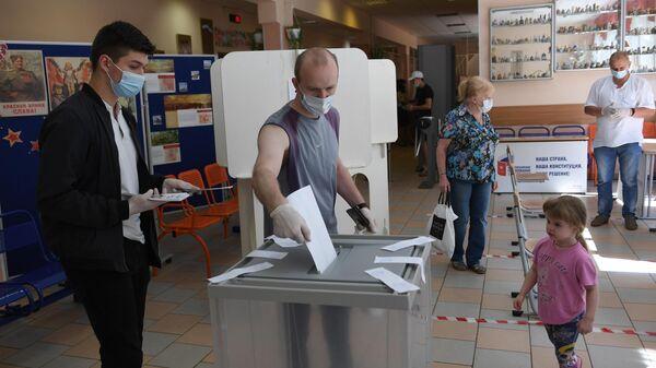 Мужчина во время голосования по вопросу принятия поправок в Конституцию РФ на избирательном участке в Москве