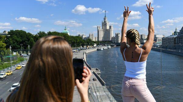 Посетители фотографируются на Парящем мосту в природно-ландшафтном парке Зарядье в Москве