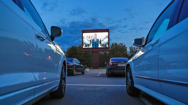 Легковые автомобили со зрителями во время киносеанса в автокинотеатре