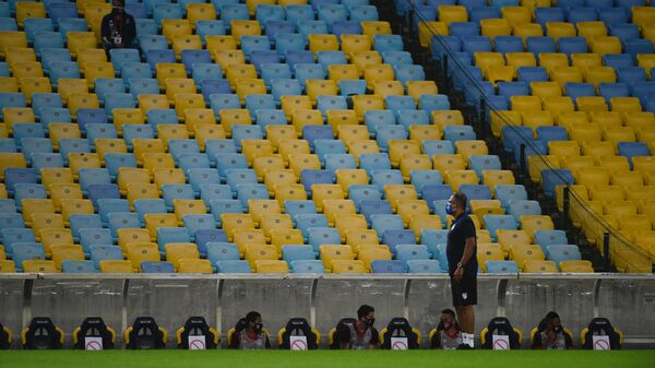 Flamengo team players remain sitting on the bench respecting security distances during a Carioca Championship 2020 football match against Bangu at the Maracana stadium, in Rio de Janeiro, Brazil, on June 18, 2020, which is played behind closed doors as the city gradually eases its social distancing measures aimed at curbing the spread of the COVID-19 coronavirus. (Photo by MAURO PIMENTEL / AFP)