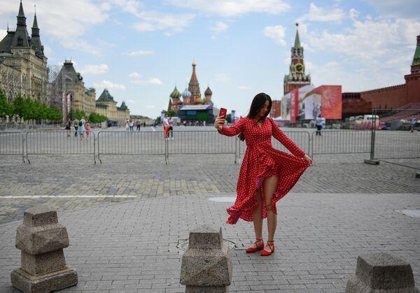Девушка фотографируется на Красной площади в Москве