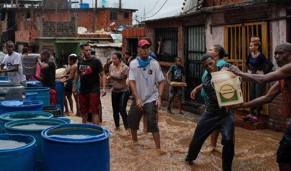 Люди набирают питьевую воду в различные емкости. В связи с трудностями в водоснабжении, жители некоторых районов Каракаса вынуждены ждать дождя, чтобы иметь возможность получить воду