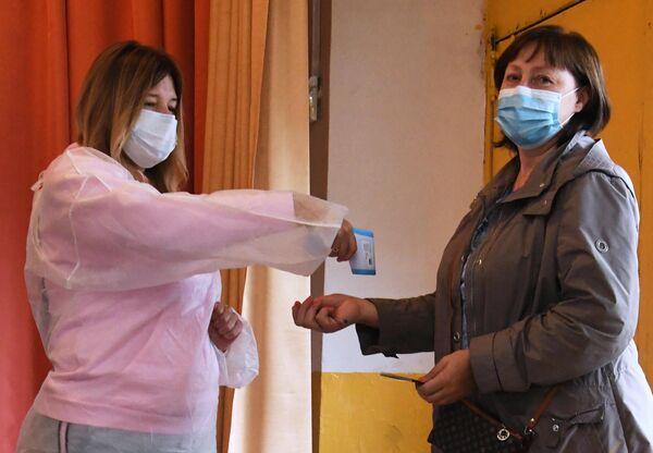 Женщине измеряют температуру при входе на избирательный участок во Владивостоке, где проходит голосование по вопросу внесения поправок в Конституцию РФ