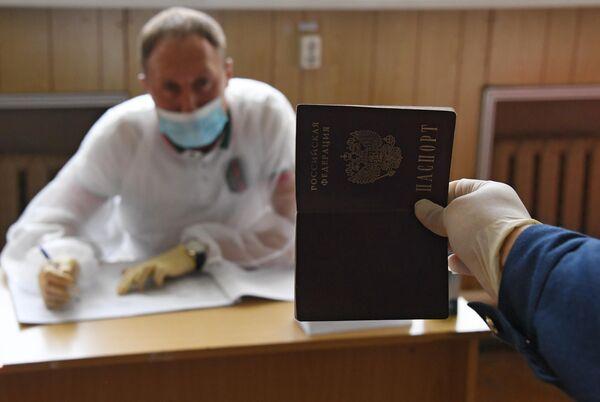 Курсант Морского государственного университета имени адмирала Г. И. Невельского предъявляет свой паспорт во время голосования по вопросу одобрения изменений в Конституцию России во Владивостоке