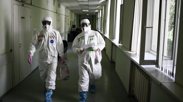 Члены избирательной комиссии в защитных костюмах в центральной клинической больнице РЖД-Медицина в Москве