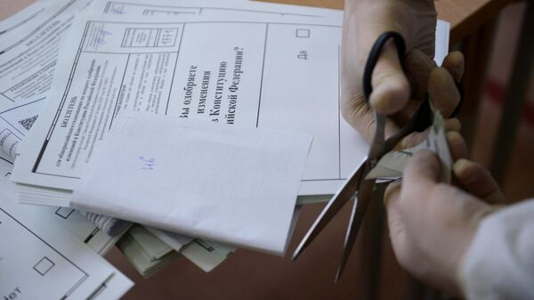 Член избирательной комиссии проводит процедуру гашения неиспользованных бюллетеней на избирательном участке №1331 в Екатеринбурге