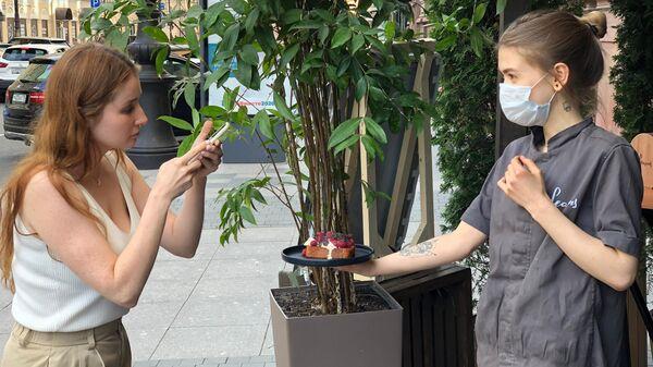 Девушки фотографируют новый десерт в гастрономическом ресторане в центре Санкт-Петербурга