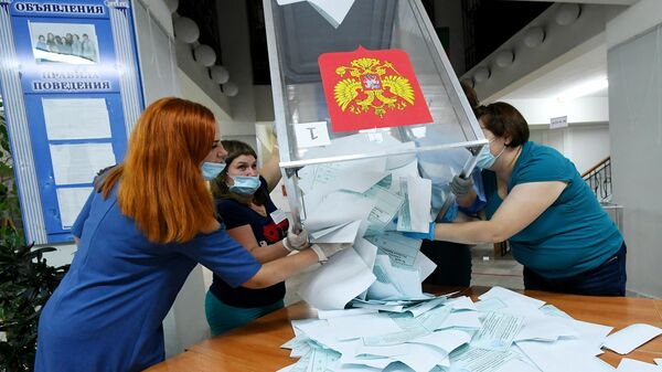 Члены избирательной комиссии вынимают бюллетени из урн на избирательном участке №101 во время подсчета голосов по итогам голосования по поправкам в Конституцию РФ в Саяногорске