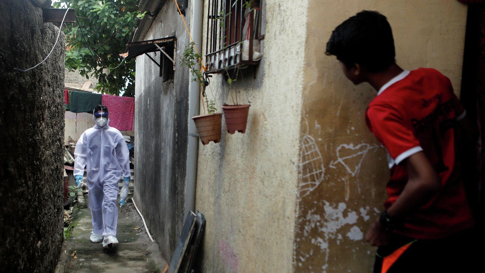 Медицинский работник в защитном костюме идет по улице в Мумбаи, Индия  - РИА Новости, 1920, 07.09.2020