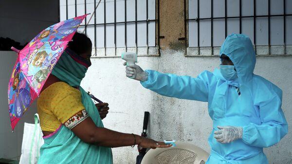 Медицинский работник измеряет температуру и пульс женщины в Мумбаи