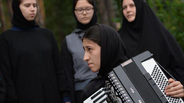 Монахиня играет на музыкальном инструменте на территории Среднеуральского женского монастыря