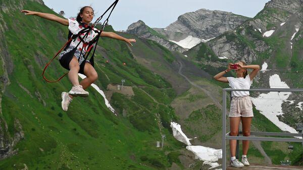 Отдыхающие на аттракционе высокогорные качели на горном курорте Красная Поляна