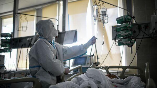 Врач проверяет капельницу у пациента в реанимации городской клинической больницы