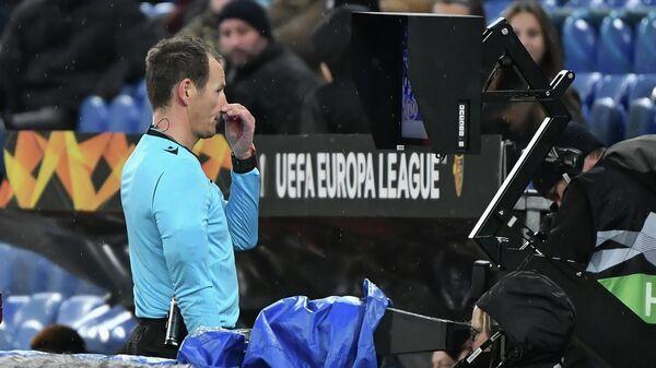 Арбитр обращается к системе VAR во время матча Лиги Европы УЕФА