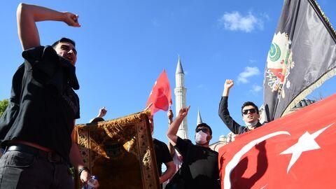 Местные жители с турецкими флагами у собора Святой Софии в Стамбуле, который снова снова стал мечетью