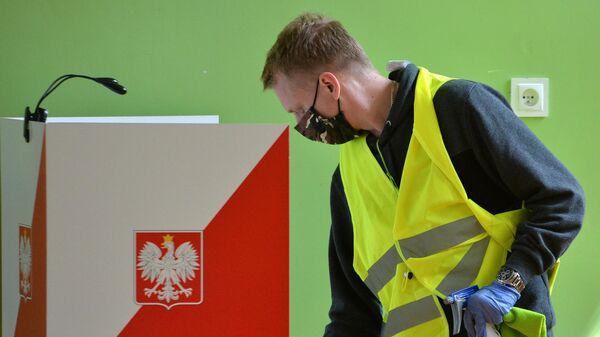 Сотрудник избирательной комиссии проводит дезифекционную обработку кабинок во время голосования на выборах президента Польши