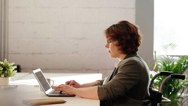 Женщина в инвалидном кресле работает за компьютером