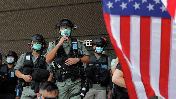 Сотрудники полиции Гонконга во время акции протеста у здания консульства США
