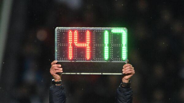 Арбитр держит табло, символизирующее о замене футболистов