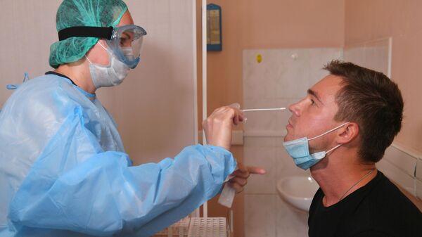 Пациент во время взятия мазка на коронавирус COVID-19 в городской поликлинике №109 ДЗМ в Москве