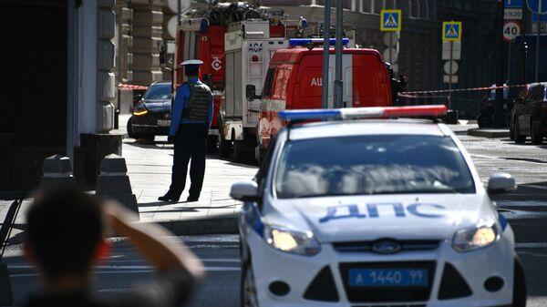 Сотрудник полиции и автомобили экстренных служб недалеко от места обнаружения подозрительного предмета в центре Москвы