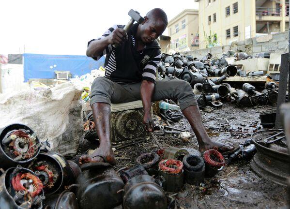 Мужчина работает над выброшенными компрессорами в центре по переработке в Абудже, Нигерия