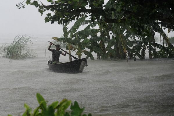Человек плывет на лодке во время наводнения в Бангладеш
