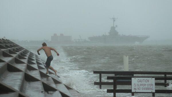 Мужчина на побережье в городе в Корпус-Кристи, Техас, где бушует ураган Ханна