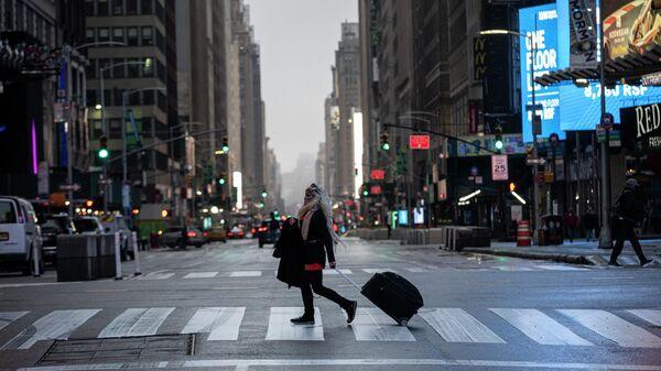Девушка с чемоданом на Таймс-сквер в Нью-Йорке во время пандемии коронавируса
