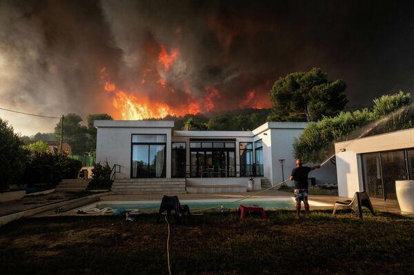 Мужчина поливает свой дом из шланга прежде чем покинуть его из-за наступающего лесного пожара в Ла-Куроне, Франция