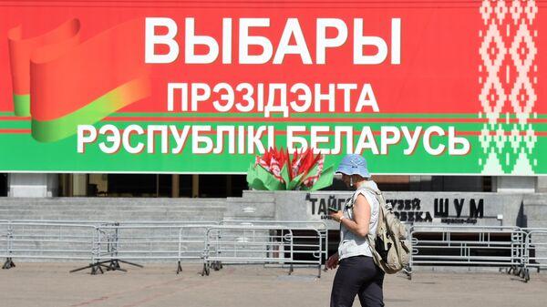 Женщина перед избирательным участком  на выборах президента Белоруссии в Минске