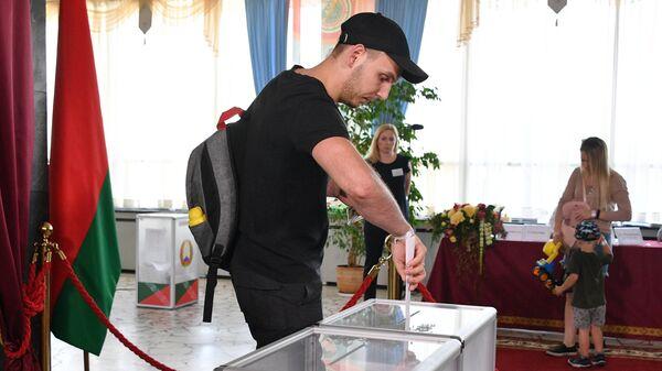 Молодой человек голосует на выборах президента Белоруссии на избирательном участке в Минске