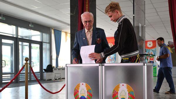 Люди голосуют на выборах президента Белоруссии на избирательном участке в Минске