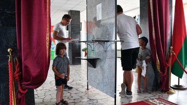 Мужчины голосуют на выборах президента Белоруссии на избирательном участке в Минске