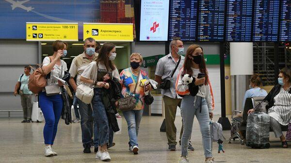 Пассажиры в международном аэропорту Шереметьево в Москве