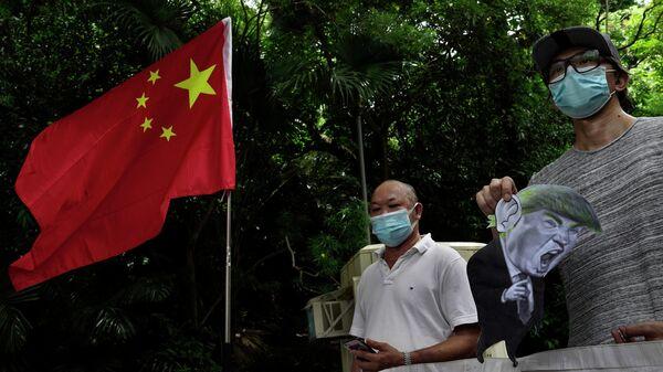 Участники акции протеста против санкций США у консульства США в Гонконге