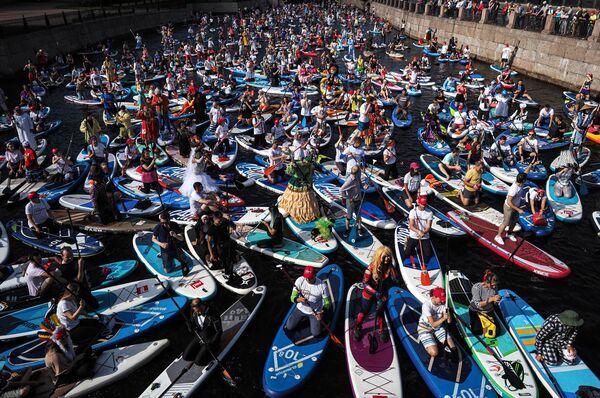 Участники международного фестиваля SUP-серфинга Фонтанка-SUP на реке Мойке в Санкт-Петербурге