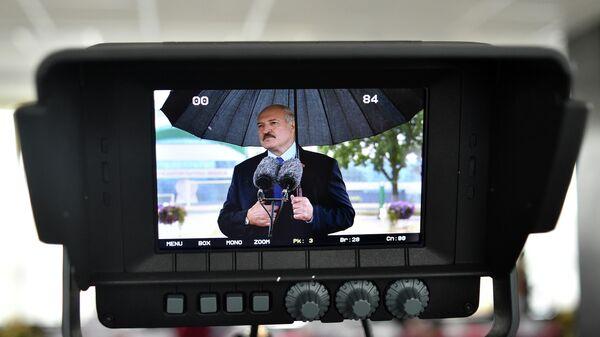 Президент Белоруссии Александр Лукашенко на экране во время разговора со СМИ в Минске. 9 августа 2020