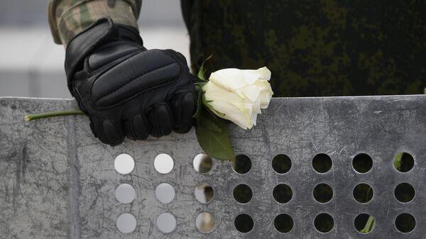 Цветок в руке военнослужащего на акции протеста в Минск