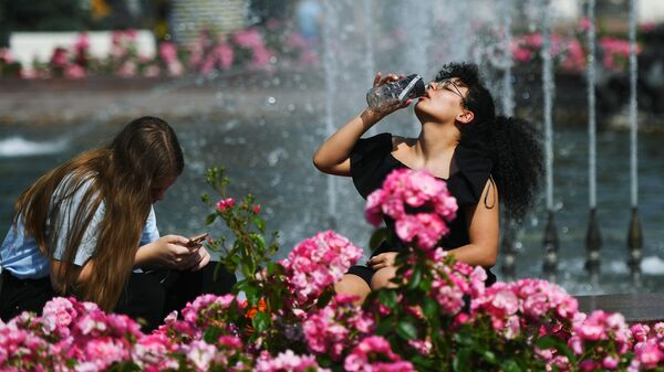 Люди отдыхают у фонтана в жаркий день на территории парка ВДНХ в Москве