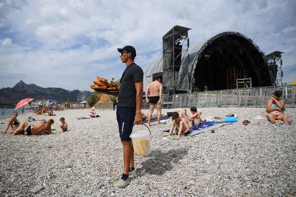Отдыхающие на пляже в Коктебеле, где проходит подготовка к открытию ежегодного международного джазового фестиваля Koktebel Jazz Party