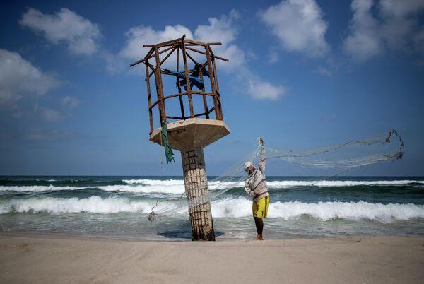 Палестинский рыбак чистит рыболовную сеть после решения Израиля закрыть рыболовную зону в Газе