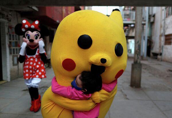 Человек в костюме Пикачу обнимает ребенка во время Дня защиты детей в Буэнос-Айресе, Аргентина