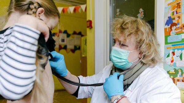 Врач осматривает ребенка, проверяет работу дыхательной системы