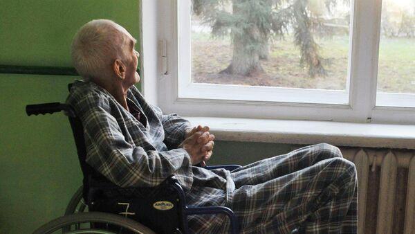 Пожилой мужчина в инвалидном кресле