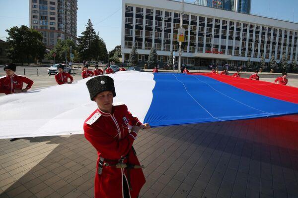 Казаки почётного караула Кубанского казачьего войска разворачивают триколор на Главной городской площади Краснодара во время празднования Дня Государственного флага РФ