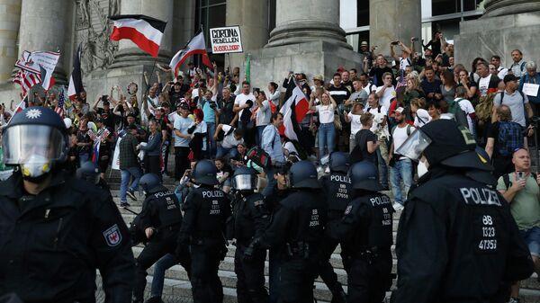 Полицейские перед зданием Рейхстага во время митинга против правительственных ограничений после вспышки COVID-19 в Берлине, Германия