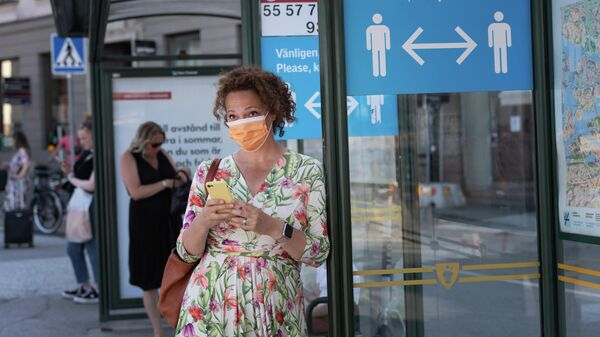 Женщина в защитной маске на автобусной остановке с плакатом, призывающим держать социальную дистанцию, Стокгольм, Швеция